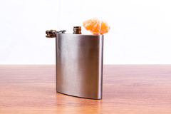 Steel flask with alcohol is on the table, along with a slice of tangerine. Alcohol addiction. Royalty Free Stock Image