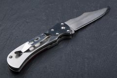 Steel folding knife with an open blade on a stone surface. Steel arms. The concept of weapon, hunting or crime. Material evidence royalty free stock photo