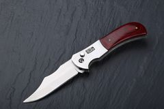 Steel folding knife with an open blade and wooden handle on a stone surface. Steel arms. The concept of weapon, hunting or crime. Material evidence royalty free stock images