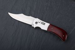 Steel folding knife with an open blade and wooden handle on a stone surface. Steel arms. The concept of weapon, hunting or crime. Material evidence stock photo