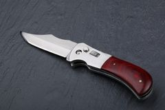 Steel folding knife with an open blade and wooden handle on a stone surface. Steel arms. The concept of weapon, hunting or crime. Material evidence stock photos