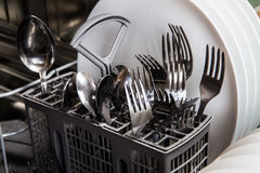 Steel forks and plates in dishwasher machine Stock Images
