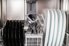 Steel forks and plates in modern dishwasher machine Royalty Free Stock Photo