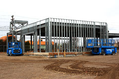 Steel Frame Construction Building. Automotive repair shop being built by steel frame. 2 high low equipment parked outside royalty free stock images