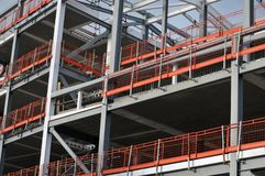 Steel framed building under construction with girders. And orange safety rails Stock Photos