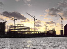 Steel framed construction site. Setting sun behind waterside steel framed building site for new office development project Royalty Free Stock Photos