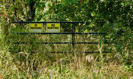 Steel gate across a wooded path. With warning signs in the foliage Royalty Free Stock Images