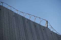 Steel gated wall with barbed wire stock photo
