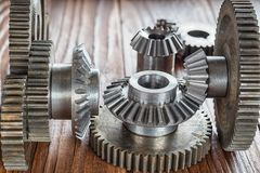 Steel gear and reducer, engineering details. Metal cogwheels. Industry Concept. Steel gear and reducer, engineering details on wooden background. Metal Royalty Free Stock Photo