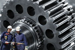 Steel gears and workers Royalty Free Stock Photography