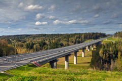 Steel girder bridge on the road that crosses Russian forest. Royalty Free Stock Photo