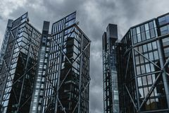 Steel and Glass Skyscrapers Block Out the Grey Sky. A neo-futuristic image of fortified steel and glass skyscrapers against an ominous grey sky stock photography