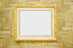 Steel gold picture frame decorative hanging on wood woven wall background royalty free stock photography