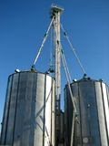 Steel grain bin and blue sky. Farming industry: steel grain storage bin stock photography