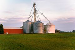 Steel grain bins at sunset. Steel Grain Bins and a Red Barn in a Green Field at Sunset stock photos