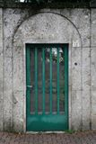Steel green door with a grid embedded in a massive concrete stone wall Straightforward style.  Stock Photo