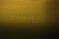 Steel grid. A steel grid with a narrow focus and gold lighting stock images