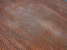 Steel Grid. Color photograph of a sheet of rusty steel with a mesh-like pattern of circular holes Stock Image
