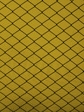 Steel grid on a yellow background Stock Photos