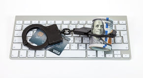 Steel handcuffs, credit card and dollars bill lying on a compute Royalty Free Stock Photo