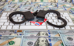 Steel handcuffs and credit cards lying on a computer keyboard on Stock Photography