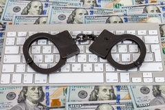 Steel handcuffs lying on a computer keyboard Stock Photos