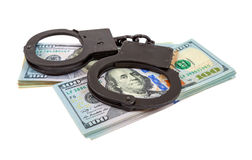 Steel handcuffs lying on a stack of dollar bills Stock Photography