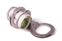 Steel handcuffs and a roll of dollars Stock Images