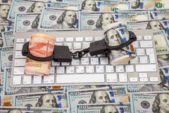Steel handcuffs, rolls of russian rubles and dollars. SAMARA, RUSSIA - JANUARY 9, 2016: Steel handcuffs, rolls of russian rubles and dollars lying on a computer stock image