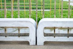 A pair of white stone benches on cement bridge at the port. With steel handrails and river view background royalty free stock images
