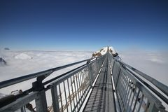 Steel hanging bridge between ice mountain peak middle blue clear sky background and white cloudy on winter season, Europe mountain Royalty Free Stock Image