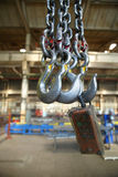 The steel hooks hanging on the background of industrial premises Royalty Free Stock Photography
