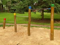 Steel horizontal bars on wooden pillars in children playground. Orange sand below bars Royalty Free Stock Photography