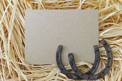 Steel horseshoes on blank brown paper and dried hay Royalty Free Stock Image