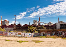 Steel industrial complex and fence with graffiti Royalty Free Stock Image