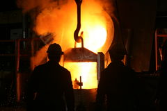 Steel Industry Molten Metal. Two foundry workmen are pouring molten metal into a large mould Royalty Free Stock Image