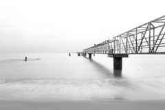 Steel jetty leading to the ocean. Black and white long exposure photo of steel jetty leading to the ocean royalty free stock images