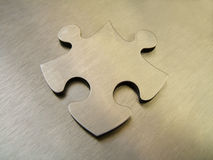 Steel jigsaw. Alone on a metallic background royalty free stock photo