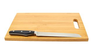 Steel kitchen knife on cutting board. Steel kitchen bread knife on the wooden cutting board isolated over white background Stock Photos