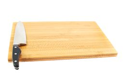 Steel kitchen knife on cutting board. Steel kitchen chef's knife on the wooden cutting board isolated over white background Stock Photography