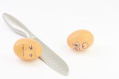 Steel knife breaks eggs Stock Photography