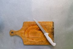 Steel knife on a cutting board on metal background. Steel knife on a cutting board on metal background Royalty Free Stock Photography