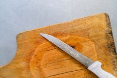Closeup steel knife on a cutting board on metal background. Steel knife on a cutting board on metal background Stock Image