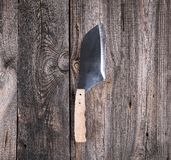 Steel knife for cutting meat with a wooden handle. On a gray background from old boards, top view stock photos
