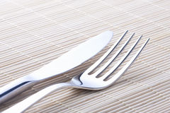 Steel knife and fork on the tablecloth bright east Royalty Free Stock Image