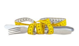 Steel knife and fork tied with measuring tape Royalty Free Stock Photo