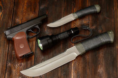 Steel knives, flashlight and gun on a wooden background, close-up Stock Image