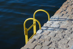 Steel ladder. Yellow  steel ladder into the water Stock Photos