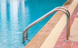 Steel ladder in a blue swimming pool Stock Photo