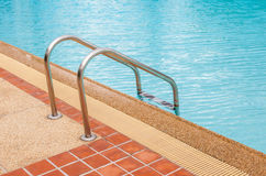 Steel ladder in blue swimming pool Stock Images